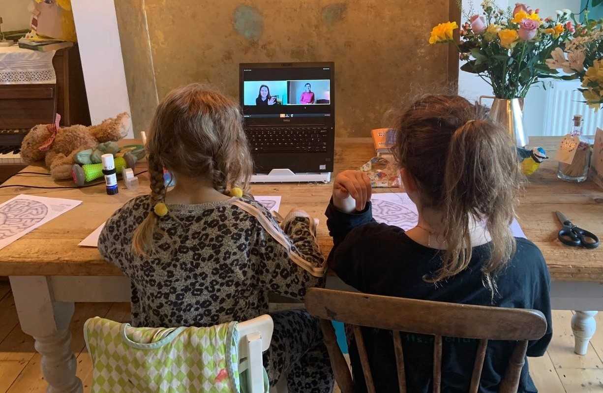 Two girls sat at a kitchen table, watching a webinar on a laptop